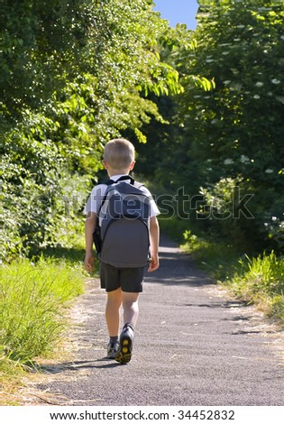 Young boy wearing a backpack ready for school - stock photo