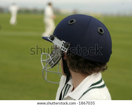 Young boy wearing a batsman,s helmet watches the team play - stock photo