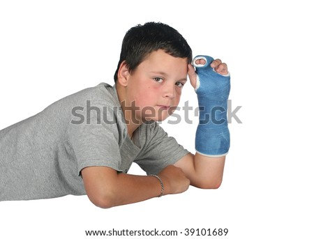 Young boy wearing a cast with a tear coming from his eye due to the pain - stock photo
