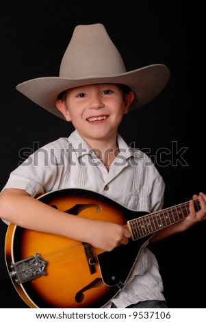 Young boy wearing a cowboy hat isolated on black playing the mandolin