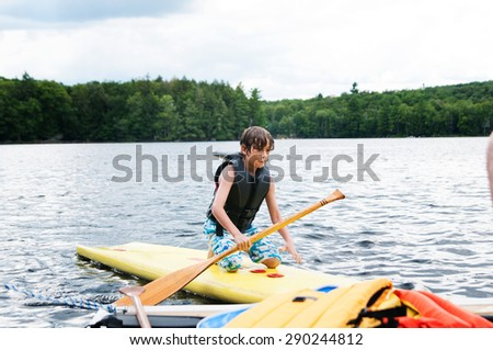 young boy wearing a life jacket paddle boarding on a lake