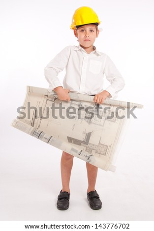 Young boy wearing a safety helmet, holding architecture blueprints - stock photo