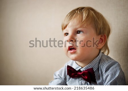 Young Boy Wearing Bow Tie Smiling and Looking Up Against Plain Wall with Copyspace - stock photo