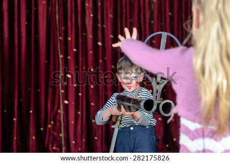 Young Boy Wearing Clown Make Up Smirking and Aiming Large Shot Gun at Blond Girl Holding Hands Up in Protest in Foreground on Stage in front of Red Curtain, Social Commentary on Youth and Violence - stock photo