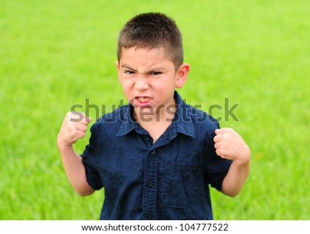 Young boy who is angry with his fists raised - stock photo