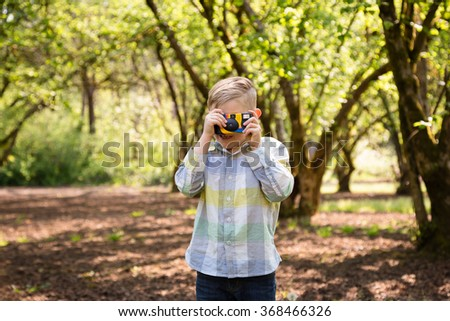 Young boy with a camera is a future photographer in this lifestyle portrait. - stock photo