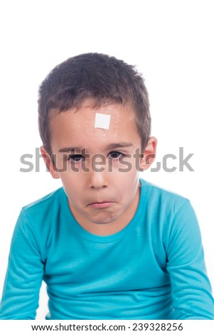 Young boy with a plaster on his forehead and sad expression