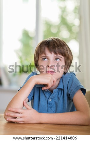 Young boy with a puzzled expression frowning as he stares thoughtfully up into the air trying to find the answer to a problem - stock photo