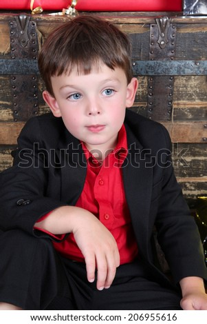 Young boy with a serious expression waiting to open gifts