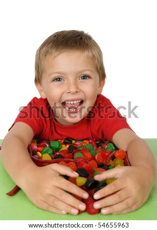 Young boy with a table full of colorful sweets - stock photo