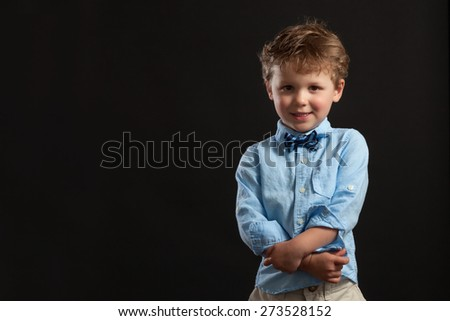 Young boy with arms crossed wearing bow tie.