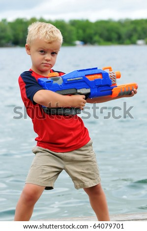Young Boy with Attitude Holds a Water Gun - stock photo