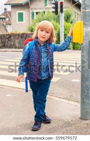 Young boy with backpack crossing the road, cute little boy walking to school - stock photo