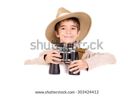 Young boy with binoculars playing Safari over a white board - stock photo