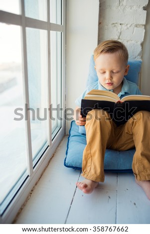 Young boy with book near window - stock photo