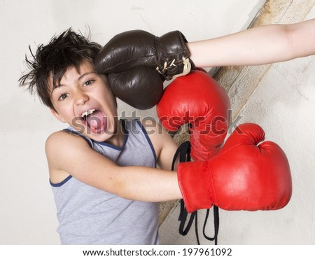 young boy with boxing gloves is getting punched - stock photo