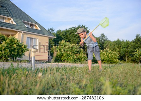 Young Boy with Bug Net Exploring Long Grass on Lawn in front of Home - stock photo