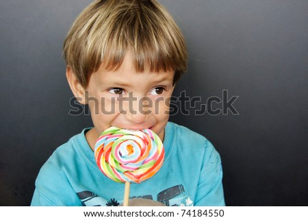 young boy with colorful lollipop - stock photo