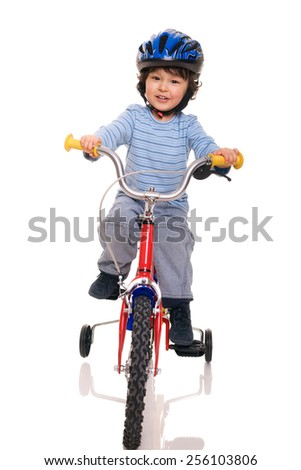 young boy with curly brown hair happily riding on a bicycle on isolated background - stock photo