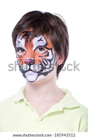 Young boy with face painting of a tiger - stock photo