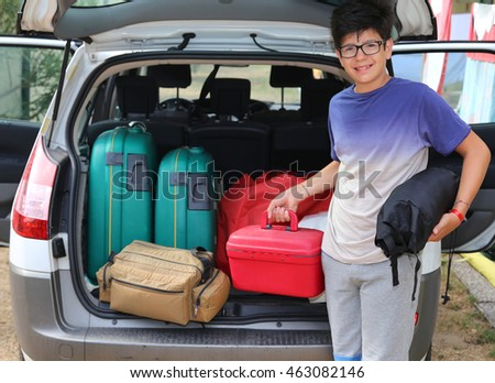young boy with glasses loaded the trunk of the car