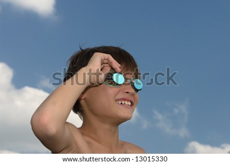 Young boy with goggles laughing, against background of blue summer sky