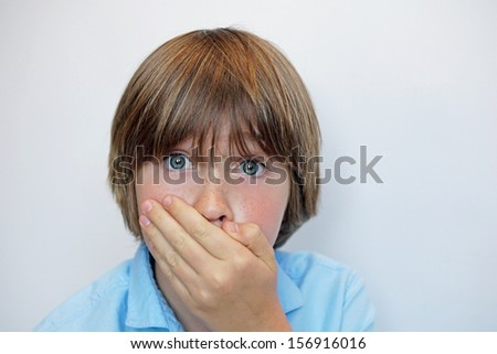 Young boy with hand over mouth in surprised or shocked expression - stock photo