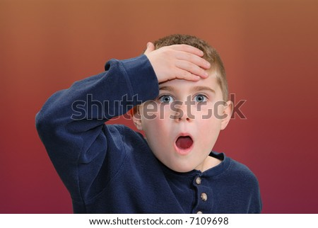 Young boy with hand to head - stock photo
