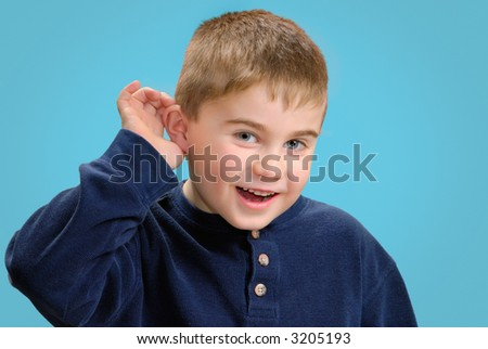 Young boy with his hand up to his ear to hear better - stock photo