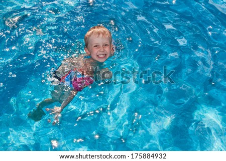 Young boy with inflatable over-sleeves swims in the pool outdoors - stock photo