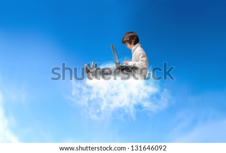 young boy with laptop sitting on a cloud in the sky - stock photo