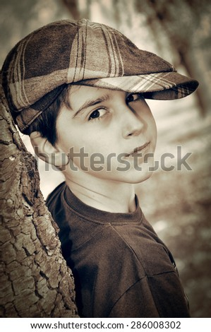 Young boy with newsboy cap leaning on a tree and playing detective. Vintage style photo  - stock photo