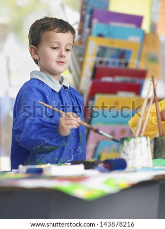 Young boy with paintbrush painting in art class - stock photo