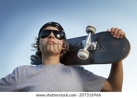 Young boy with skateboard in hand against the sky - stock photo