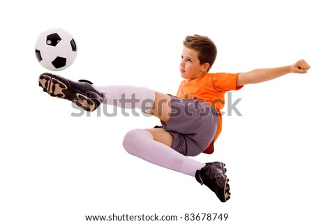 Young boy with soccer ball doing flying kick, isolated on white - stock photo