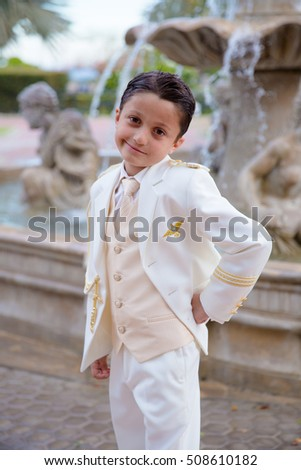 Young boy with white sailor suit smiling in his First Communion standing in front of a fountain