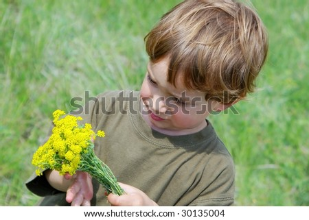young boy with yellow flowers in hands on natural background