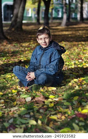 Young boy with yellow leaves on his head sitting on the ground in autumn park - stock photo
