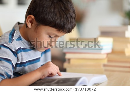 Young boy working on homework surrounded by books - very shallow depth of field