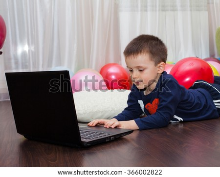 Young boy working on laptop computer concept for education, learning, internet, homework and social media, lying on the floor - stock photo
