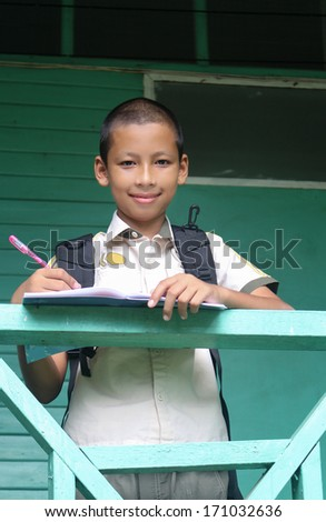 Young boy writing at school.