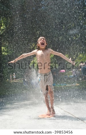 young boy yells with delight in a refreshing fountain on a hot summer day