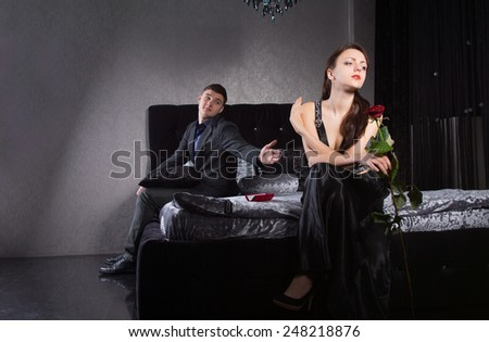 Young Boyfriend Asking Forgiveness to Mad Girlfriend While Sitting at the Bedroom. - stock photo