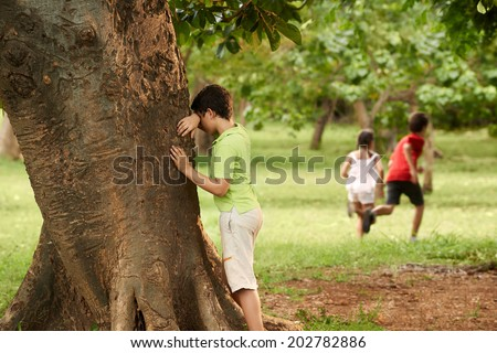young boys and girls playing hide and seek in park, with kid counting leaning on tree - stock photo