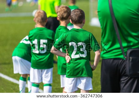 Young boys and soccer coach watching football match. Youth reserve players ready to play football tournament; sport background - stock photo
