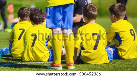 Young boys as a soccer football sitting together on a bench. Boys ready to play the game