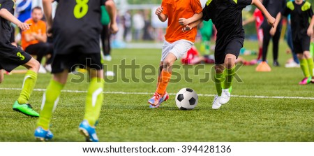 Young boys children in uniforms playing youth soccer football game tournament. Horizontal sport background. - stock photo