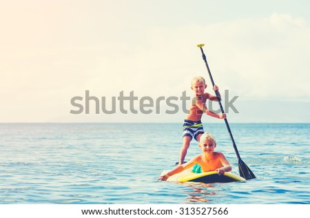 Young Boys Having Fun Stand Up Paddling Together in the Ocean - stock photo