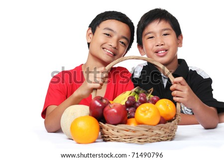 Young boys holding a basket of fruits - stock photo