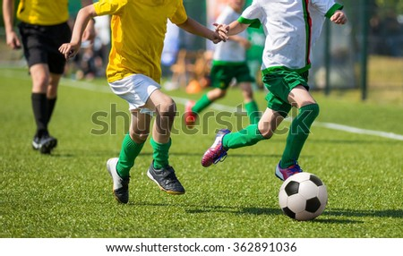 young boys kids children playing football soccer game. Running players in yellow and white uniforms - stock photo